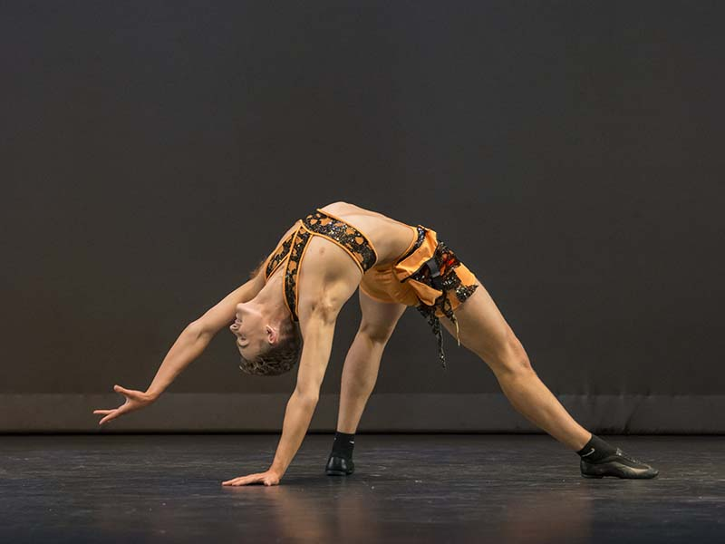 Chase Leathard dancing in costume on stage in a back bend position