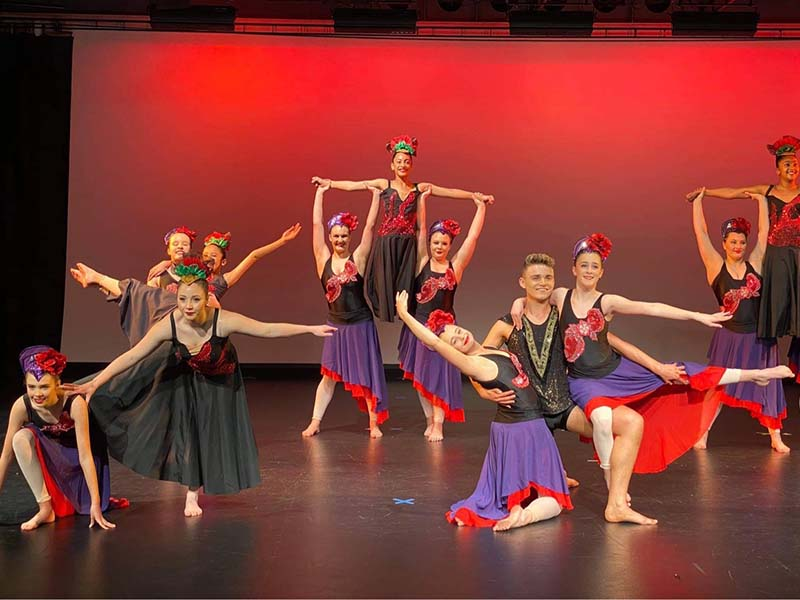 VCM Academy ballet students dancing on stage in red and purple skirts
