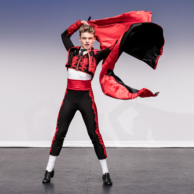 Chase Leathard dances on stage in a matador costume swinging a red cape
