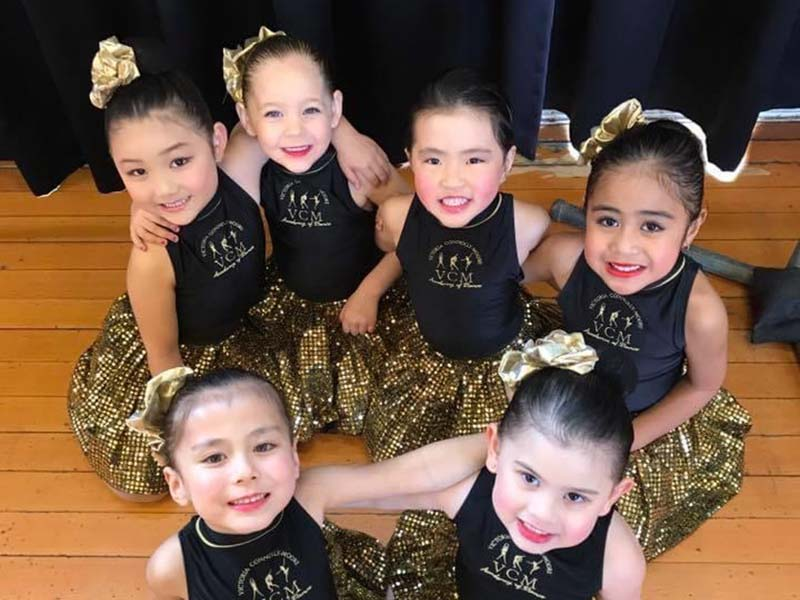 VCM Academy beginner dance classess students sit together in cute sequinned uniforms