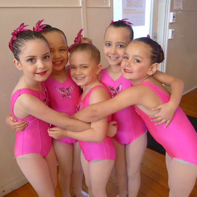 junior ballet students hugging each other in pink costumes at a leading dance academy