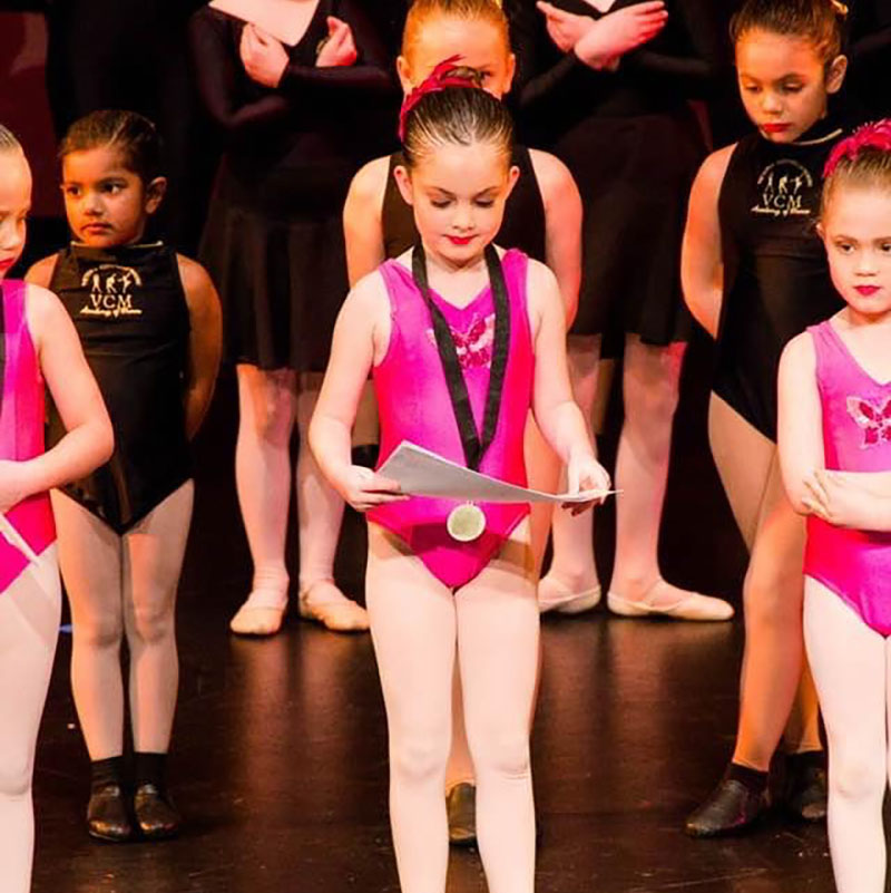 Junior dance student in pink leotard on stage receiving a medal and certificate