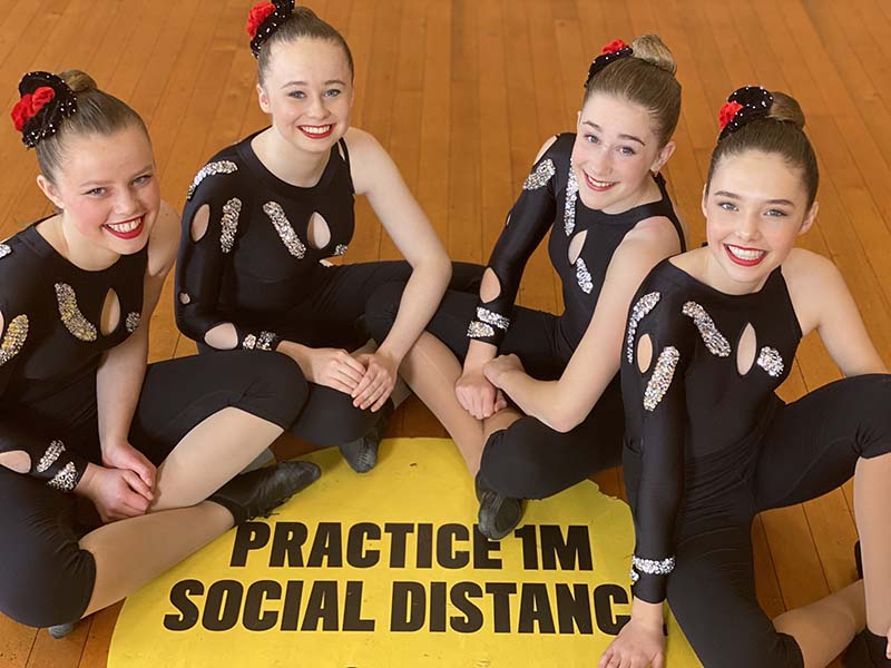 VCM student dancers sitting together smiling in their dance uniforms