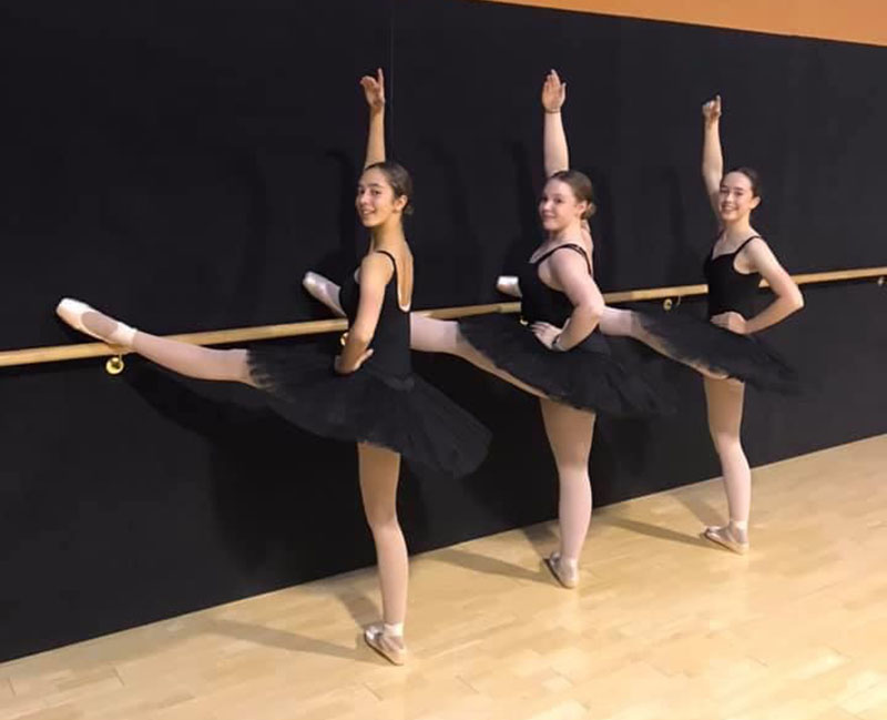 Senior ballet dance classes at VCM Academy students stand at barre with legs extended